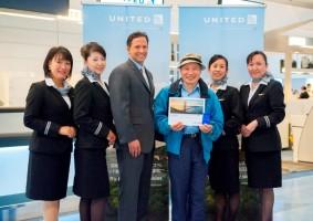 初便搭乗手続き第1号の乗客を囲むUAセフォリア副社長、客室乗務員(UNITED)
