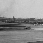 RW15R(A滑走路) からツインボナンザが離陸 あちら側にいる機体はJALのDC-6B?、全日空のDC-3貨物機も見える。1964年(昭和39年)頃。(森)